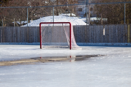 Ice hockey rink with hockey net on melting ice in the early spring.