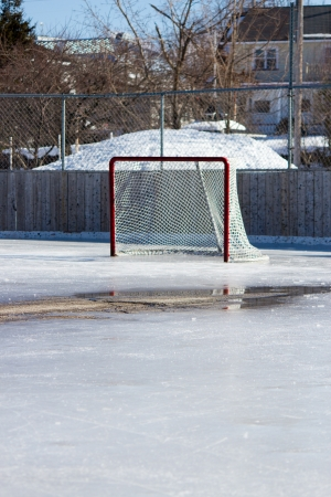 Ice hockey rink with hockey net on melting ice in the early spring. Stock Photo - 13899436