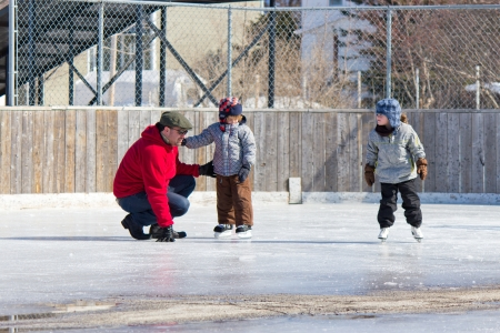Family having fun at the outdoor skating rink in winter. Stock Photo - 13899435