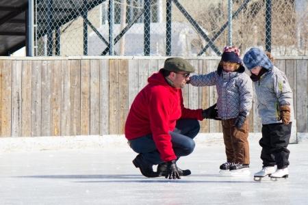 patinaje: Familia que se divierte en la pista de patinaje al aire libre en invierno.