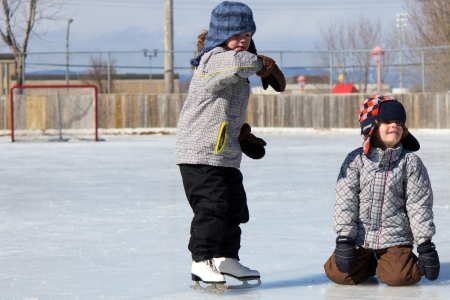 Children playing and skating at the outdoor skating rink during winter. Stock Photo