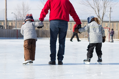 rink: Family having fun at the outdoor skating rink in winter.