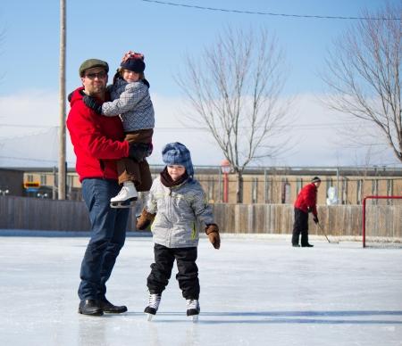 Vater mit Sohn und Tochter spielen an der Eisbahn im Winter. Lizenzfreie Bilder