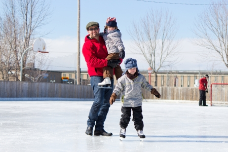 Father with son and daughter playing at the skating rink in winter.
