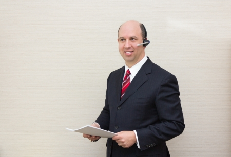 handsfree telephone: Business man with a handsfree telephone headset holding a document.