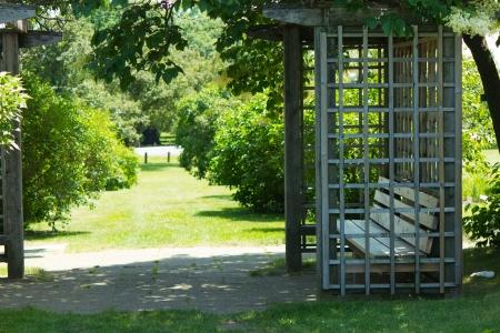 A gazebo with a bench in a peaceful garden