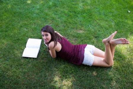 A pretty girl reads a book in her backyard.