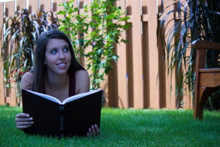 Pretty teen girl reading outside - copyspace photo