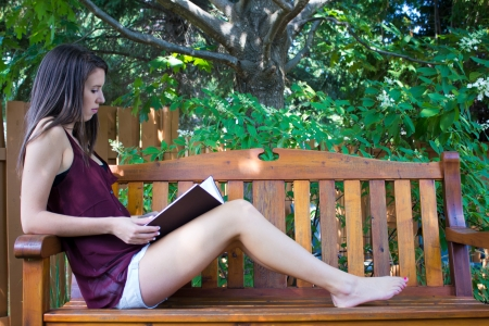Pretty teen girl reading outside on a bench - copyspace photo