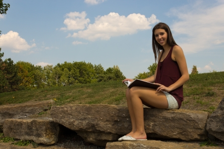 Pretty girl reading in the park - copyspace photo