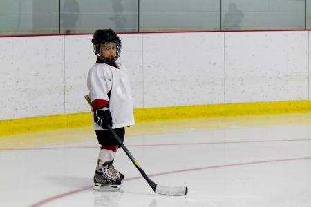 Little boy playing ice hockey Stock Photo