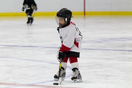 child protection: Little boy playing ice hockey Stock Photo