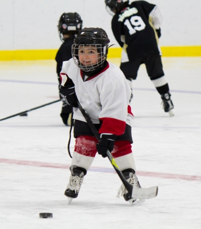 skating rink: Little boy playing ice hockey Stock Photo