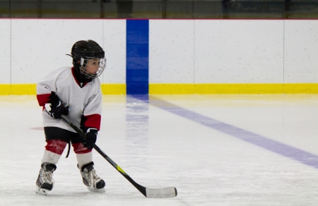 rink: Little boy playing ice hockey Stock Photo