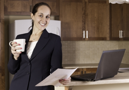 Business woman working on a laptop computer and drinking coffer in her kitchen. photo