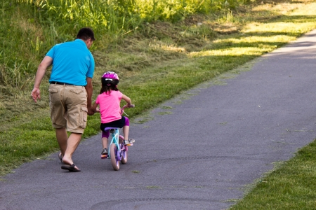 Child learning to ride a bicycle with father
