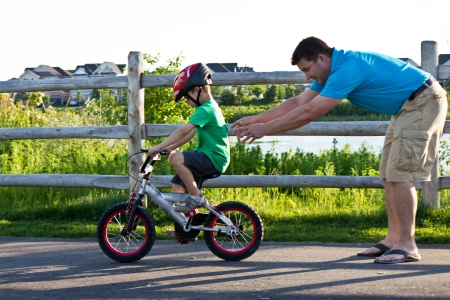 bicycling: Child learning to ride a bicycle with father