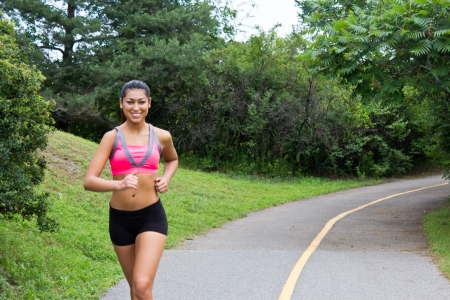 Smiling young woman running for fitness Stock Photo