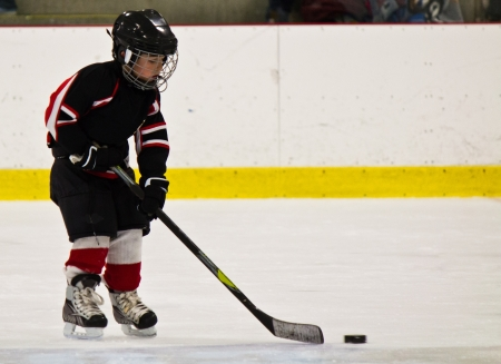 Child skating and playing hockey in an arena photo