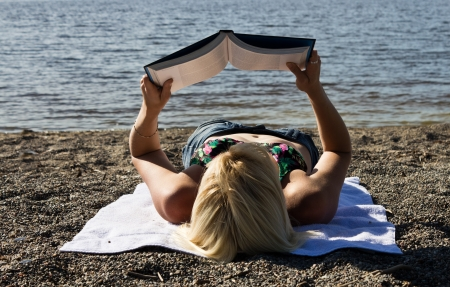 Woman reading a book on the beach photo