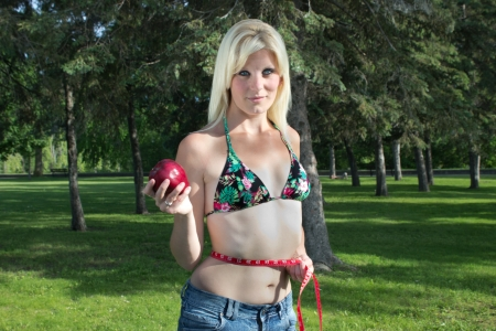 Fit young woman with apple and measuring tape aroung waist