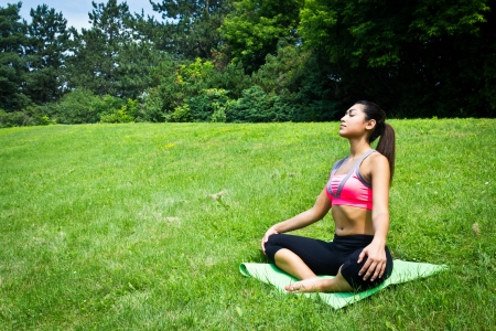 Young fit woman practices yoga in the park to meditate and relax photo