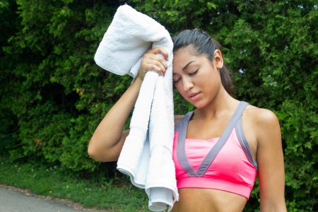 Woman towels off and rests after running photo