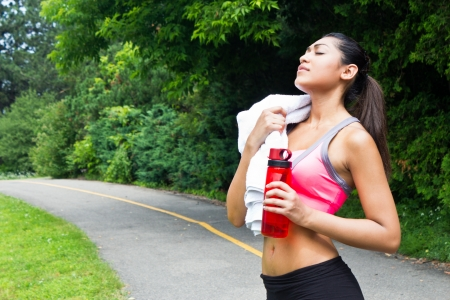 Young woman resting with towel and water bottle after running photo
