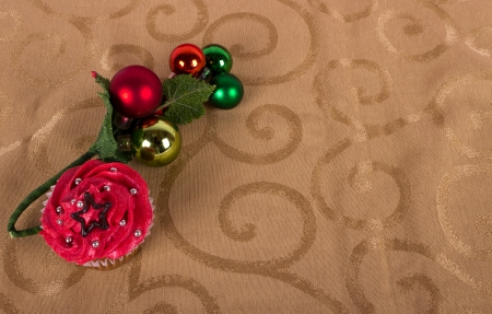 Christmas cupcake with tree ornament on gold background