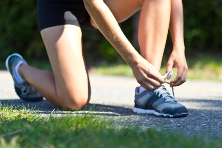 Woman tying her shoes before running photo
