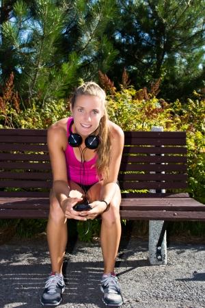 Frau sitzt auf einer Bank mit Smartphone vor einem Lauf