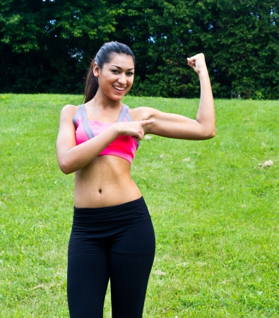 Young fit woman flexes her muscles photo