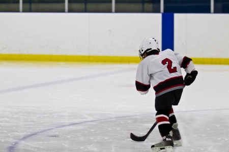 ice skating: Young child skating and playing ice hockey Stock Photo
