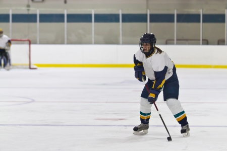 Woman ice hockey player skating during a game Stock Photo