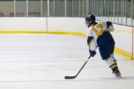 ice hockey puck: Female ice hockey player skating during a game Stock Photo