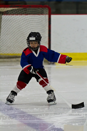 아이스 하키 연습 도중 뒤로 스케이팅하는 소년