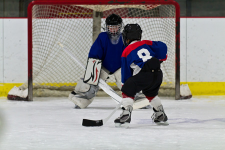 Young ice hockey player prepares to shoot on net 스톡 콘텐츠