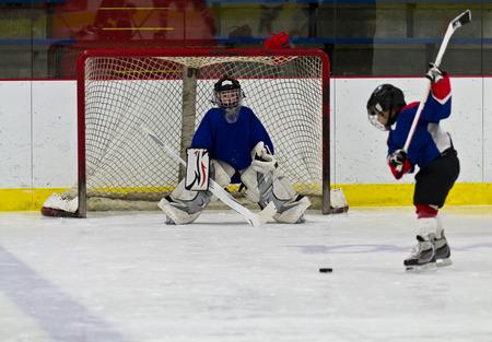 Eishockey-Spieler schie�t den Puck am Netz