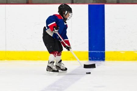 아이스 하키 연습에서 퍽으로 스케이팅하는 소년