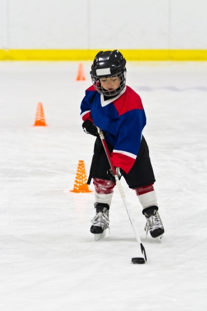 Boy skating with the puck at ice hockey practice
