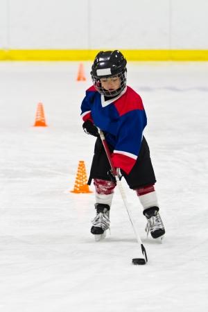 아이스 하키 연습에서 퍽 스케이트 보이 스톡 콘텐츠