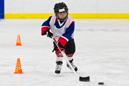 아이스 하키 연습에서 퍽으로 스케이팅하는 아이 스톡 콘텐츠