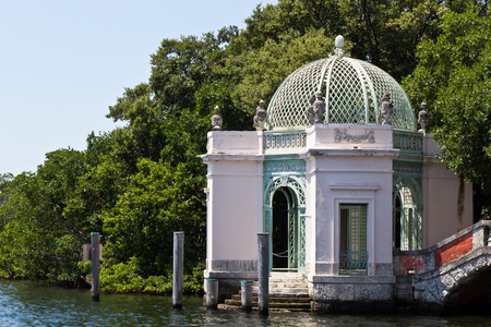 Ornate waterfront building in a garden