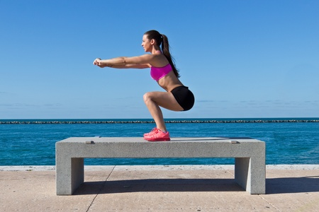 Hispanic woman doing squats on a bench by the ocean Stock Photo