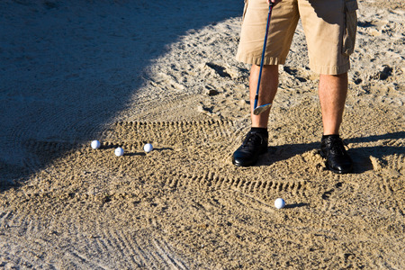 Golfer practicing from the sand bunker photo