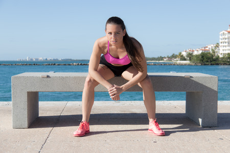 Determined, fit hispanic woman sitting on a bench photo