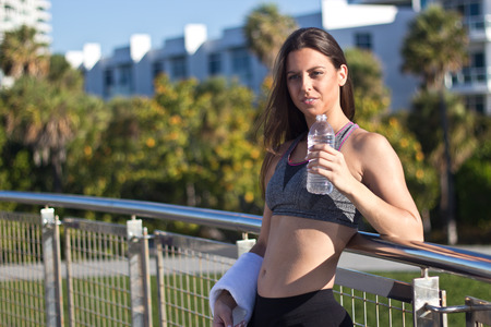 Hispanic girl drinks water during a fitness session photo