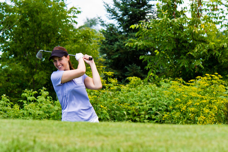 Female golfer swining her club on the fairway photo