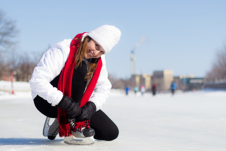 ice skating: Attractive woman getting ready to ice skate in winter Stock Photo