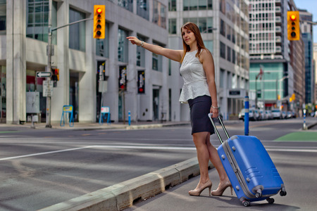 hailing: Traveling Business Woman Hails a Taxi on a city street